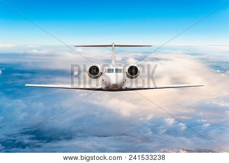 Front View Of Aircraft. Privat Jet In Flight. The Passenger Plane Flies High Above The Clouds And Bl