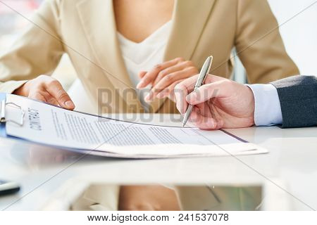 Side View Close Up Of Unrecognizable Businessman Signing Contract During Meeting With Unrecognizable