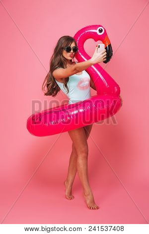 Full length portrait of a seductive young woman dressed in swimsuit posing with inflatable flamingo while taking a selfie isolated over pink background