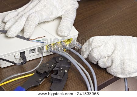 A Man Connects A Network Cable To The Modem, A Close-up