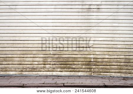 White Weathered Plastic Plank Wall And A Sidewalk. Architecture Detail Background