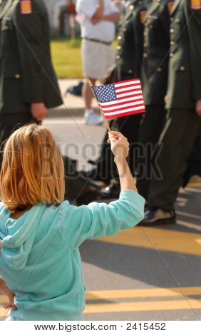 Girl Waving An American Flag During A Parade