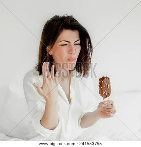Happy Smiling Young Woman Eating Ice Cream In A Bedroom. Beautiful Caucasian Girl With Short Dark Ha