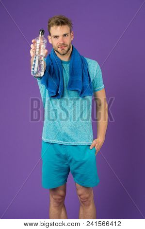 Man Hold Water Bottle On Violet Background. Sportsman With Plastic Bottle. Athlete In Blue Tshirt An
