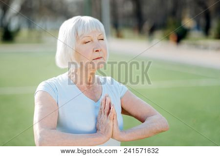Meditation. Concentrated Aged Woman Doing Yoga While Exercising In The Open Air