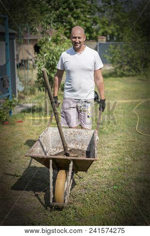 Man Pushing Wheelbarrow. Young Man Pushing A Wheelbarrow On The Farm.. Vignetting.
