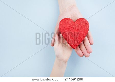 Doctor And Kid Holding Red Heart In Hands. Family Relationships, Health Care, Pediatric Cardiology C