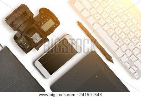 Top View Of A Desktop Of A Photographer Consisting Of A Cameras, A Keyboard, A Smart Phone On A Whit