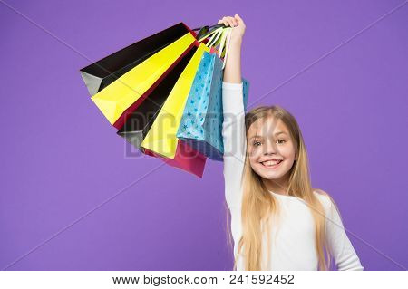 Happy Child With Paper Bags. Little Girl Smile With Shopping Bags On Violet Background. Kid Shopper