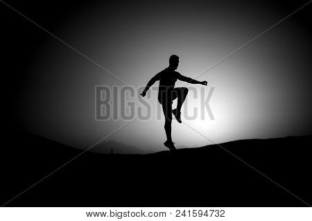 Athlete With Muscular Body In Dusk. Man Jump On Sunset Sky Background. Sport, Fitness, Activity. Fre