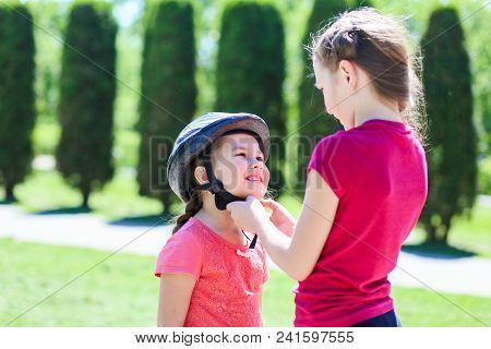 Older Sister Wears A Bicycle Helmet To A Younger Sister