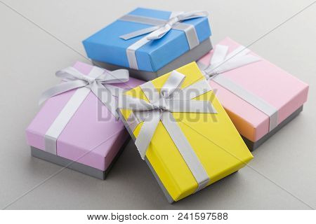 Small Colorful Gift Boxes With Ribbon Bows On Gray Background. Pink, Yellow, Blue And Violet Boxes F