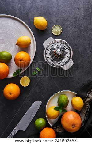Top View Of Fresh Ripe Citruses. Lemons, Limes, Oranges And Grapefruits With Knife And Citrus Squeez