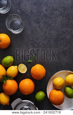 Top View Of Fresh Ripe Citruses. Lemons, Limes, Oranges And Grapefruits With Glasses And Citrus Sque