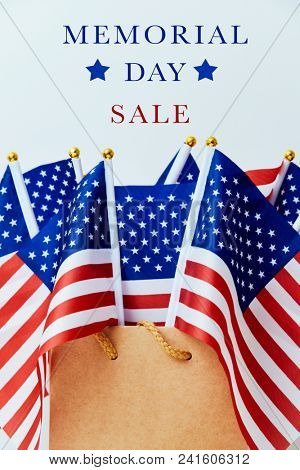 the text memorial day sale and a brown paper shopping bag with many flags of the United States