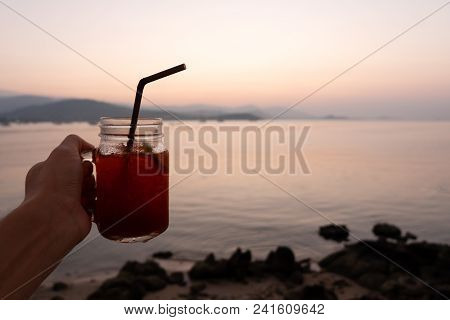Hand Holding Glass Of Lemon Ice Tea On Tropical Sea Beach In Sunset. Summer Holiday Vacation In Outd