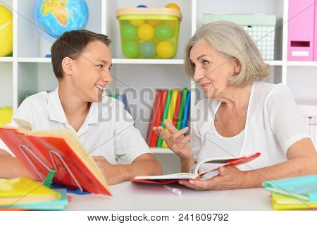 Schoolboy Doing Homework At Home With Grandmother
