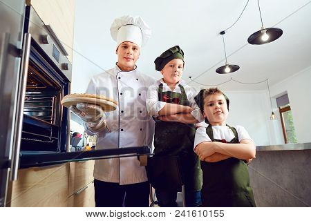 Children Bakers With Pizza In The Kitchen With A Cook.