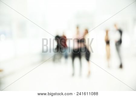 Blurred Image Of A Group Of Business People Talking In The Office Lobby. Business Background.