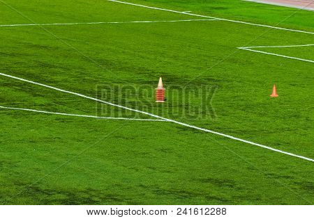 Football Field With White Markings And An Orange Cone In The Middle