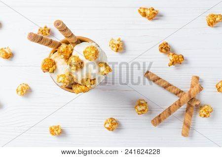 Ice Cream With Caramel And Popcorn On A White Table.