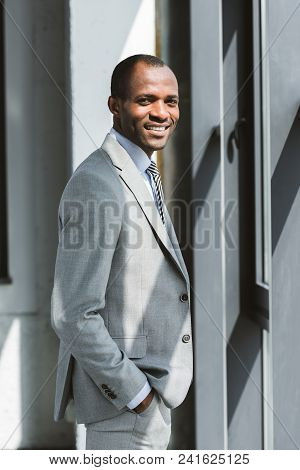 Portrait Of Handsome Young African American Businessman Standing With Hand In Pocket And Smiling At