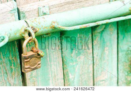 Old Iron Rusty Padlock On The Green Wooden Door.