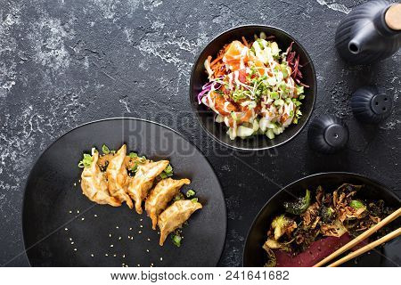 Asian Cuisine Dishes With Poke Bowl, Fried Potstickers And Sesame Brussel Sprouts On The Table Overh
