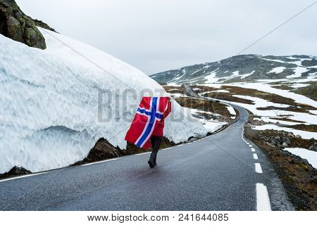 Bjorgavegen - Snowy road in Norway. Girl with the Norwegian flag on a mountain road near a wall of snow. Severe northern landscape