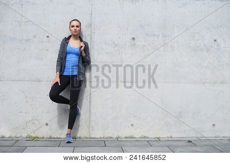 Young, Fit And Sporty Woman Standing In Front Of Concrete Cement Wall. Fitness, Sport, Urban Jogging