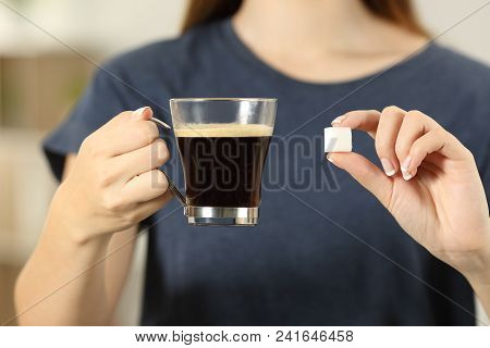 Front View Close Up Of A Woman Hands Holding Coffee Cup And A Sugar Cube At Home