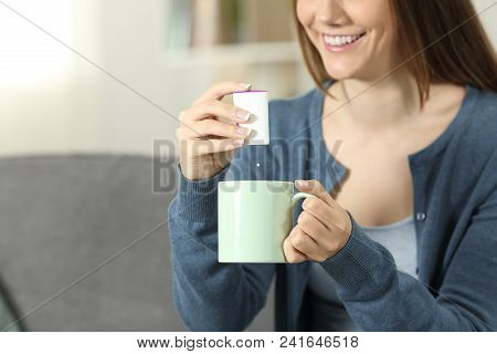 Close Up Of A Woman Hands Throwing Sacharine Pill Into A Mug Sitting On A Couch In The Living Room A