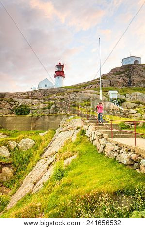 Tourist Woman And Historic Red White Lighthouse On The Edge Of Rocky Sea Coast, South Norway, Lindes