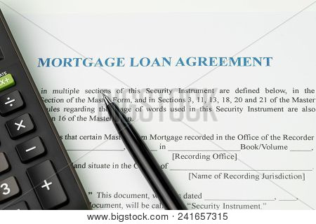 Mortgage Loan Agreement Sign Contract Concept, Pen With Calculator On Mortgage Form Or Contract, Lon