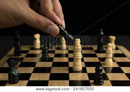 Close-up Of Hand Moving The Black Bishop, Chess Board On Dark Background