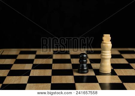 Close-up Of The Black Pawn And The White King, Chess Board On Dark Background