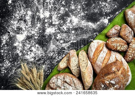 Different Bread With Flour And Spikelets Of Wheaton Black Background. Top View. Still Life. Flat Lay
