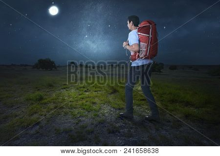 Attractive Asian Traveler With Backpack Walking On The Field At Night