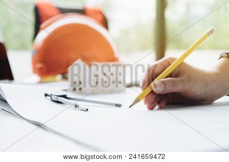 Hand Of Architect Working On Blueprint. Engineer Inspective In Workplace And Use Computer Laptop, Pe