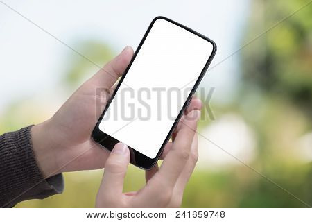 Male Hand Holding Smartphone At Park. Blank Screen Mobile Phone For Graphic Display Montage