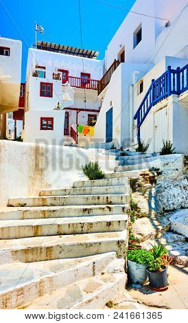 Old uphill street with white little houses in Mykonos, Greece