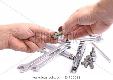 Hand With A Nut And Bolt On The Background Of Wrenches