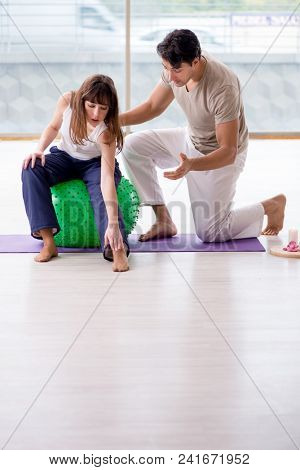 Personal coach helping woman in gym with stability ball