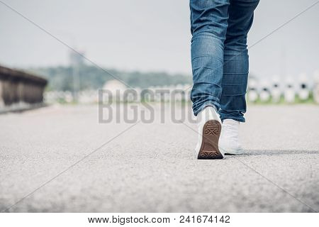 Close Up Woman Wear Jean And White Sneaker Walking Forward On Highway Road In Sunny Day,alone Travel