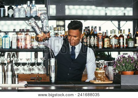 Expert And Professional Mixed Race Male Expert Bartender Is Adding Alcohol In A Shaker For The Elabo