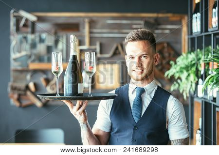 Smiling And Elegant Waiter Is Holding A Tray With Two Glasses And A Bottle Of Champagne In A Restaur