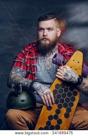 Bearded Man With Tattooes In A Red Shirt Holding Longboard.