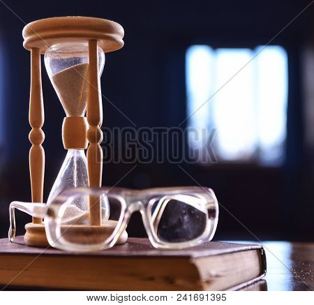 Hourglass, Old Book And Eyeglasses On Wooden Table, Dark Background. Sand Falling Down Inside Of Hou
