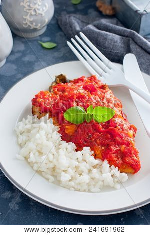 Flounder with tomato sauce and boiled rice, selective focus poster