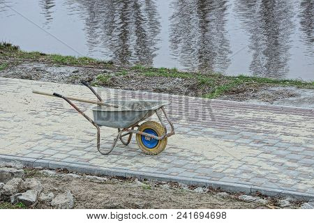 Gray Dirty Wheelbarrow Is On The Sidewalk On The Shore Of The Reservoir